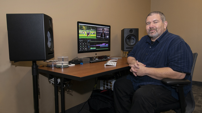 Mark Slusher sits at his computer desk, with video editing software opened.
