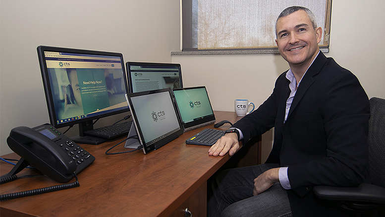 Travis Street, smiling at his desk in front of four mixed computer & tablet screens.